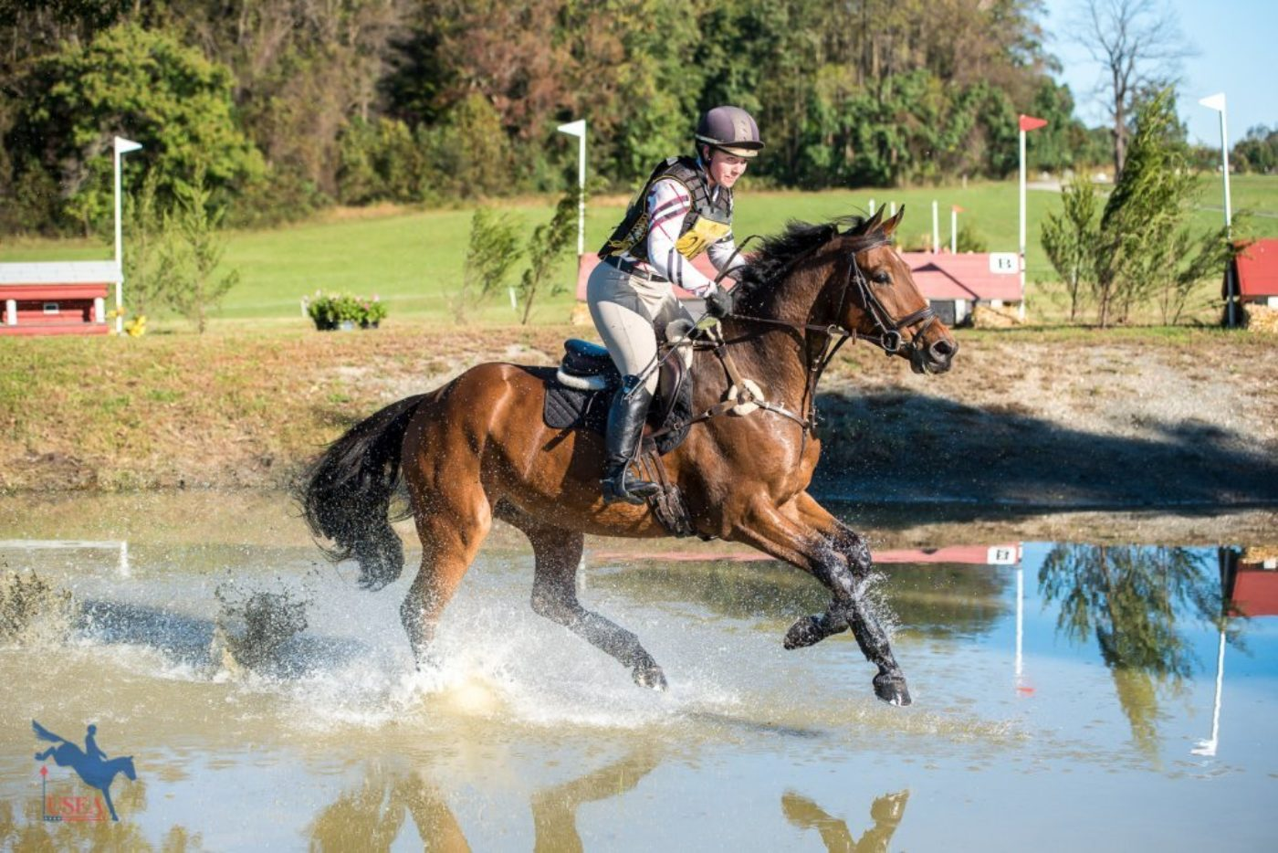 Booli Selmayr and Quality Touchdown splashing their way through the YEH Championship jumping course. USEA/Jessica Duffy Photo.